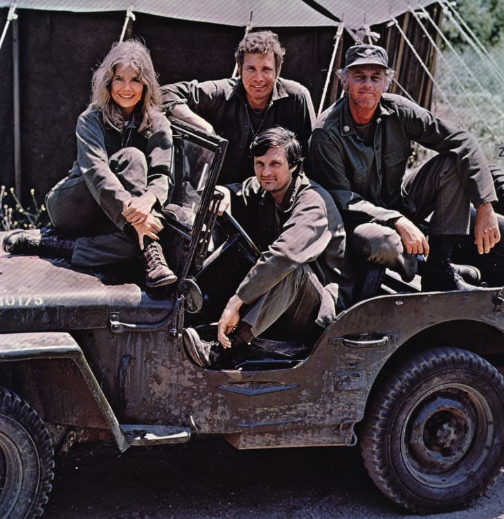 American actor, director and writer Alan Alda in the driving seat of a jeep, surrounded by Loretta Swit and other cast members of the hit television show M.A.S.H, in costume as members of a US Army medical corp.