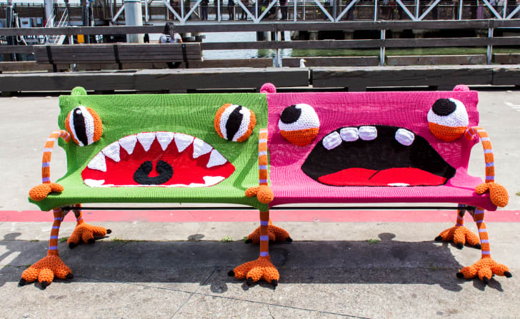 Two benches covered in bright yard and decorated to look like monsters.