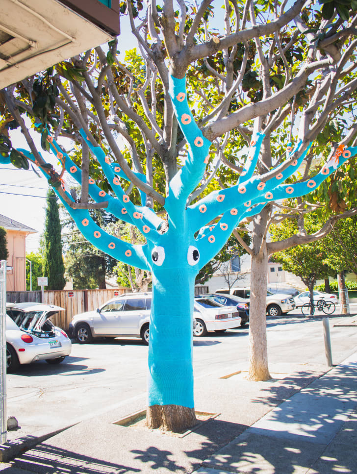 A tree covered in bright blue yard and decorated to look like a squid.