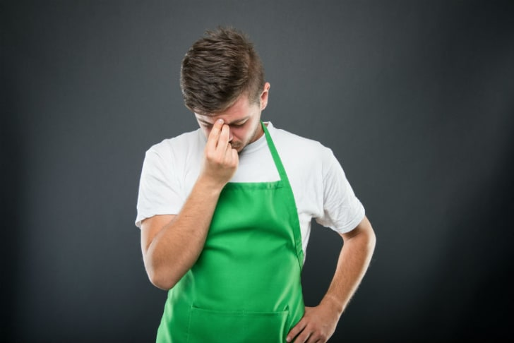 A man in an apron looks tired