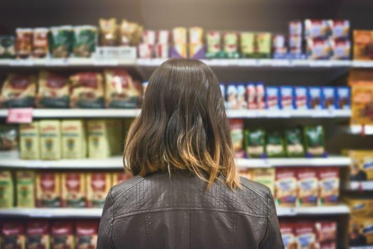 A woman examines a supermarket shelf
