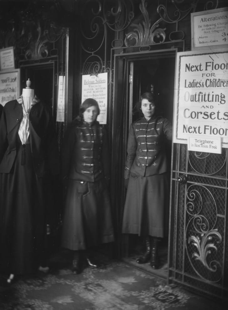 Two lift operators in a London department store, circa 1916.