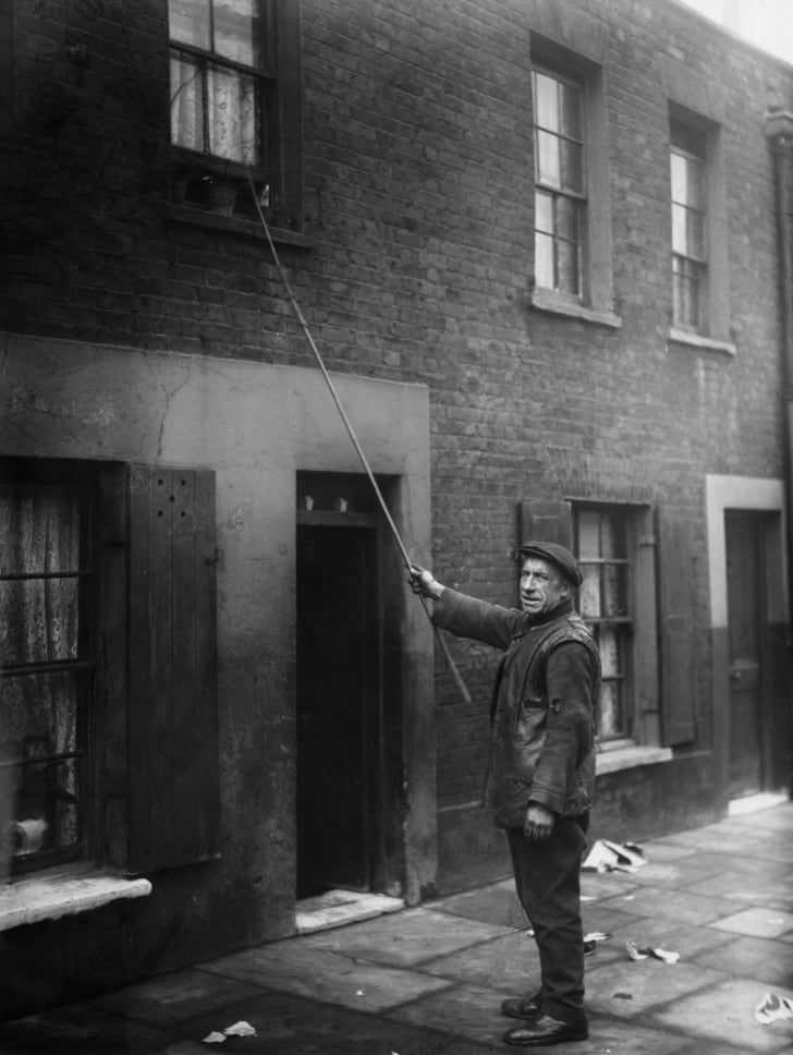 A knocker-up in London in 1929.