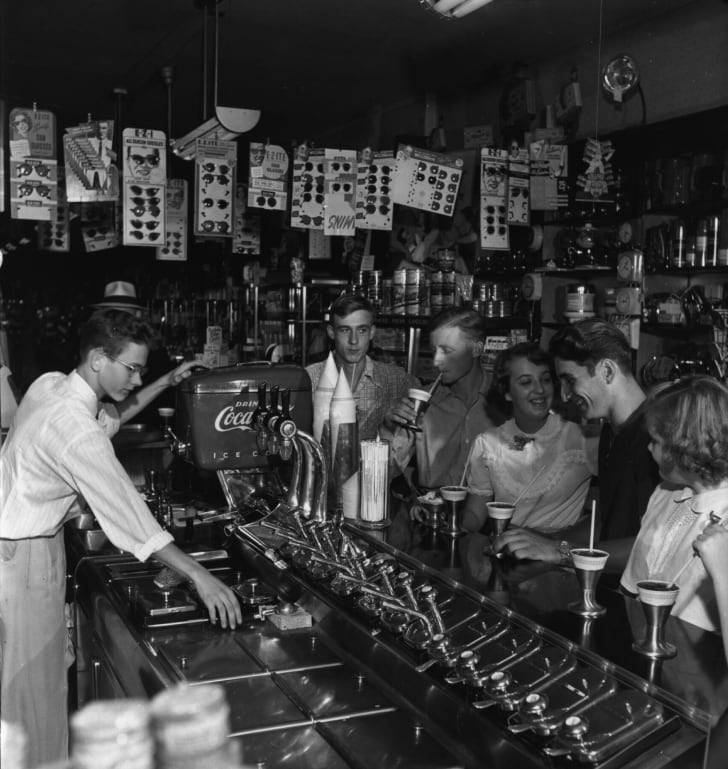 A soda jerk serves sweet drinks at a drugstore's soda fountain in 1950.