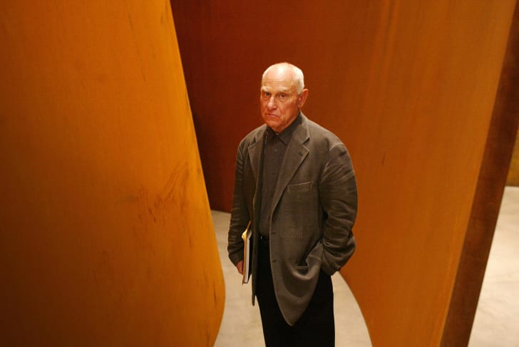 Richard Serra standing with his work.