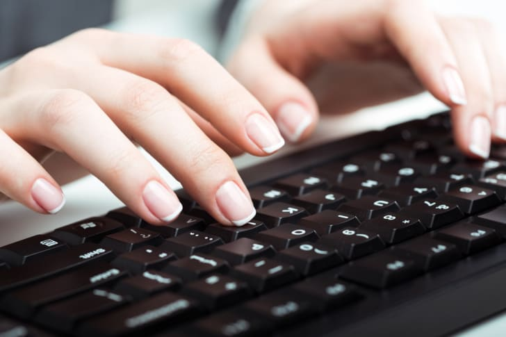 A person types on a computer keyboard