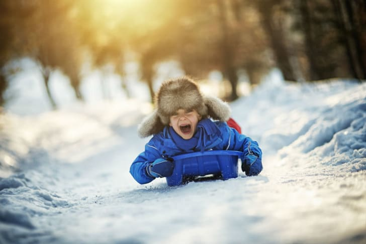 A child goes for a ride on a plastic sled
