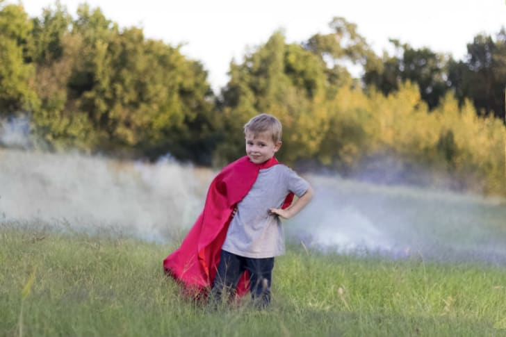 A child poses while wearing a superhero cape