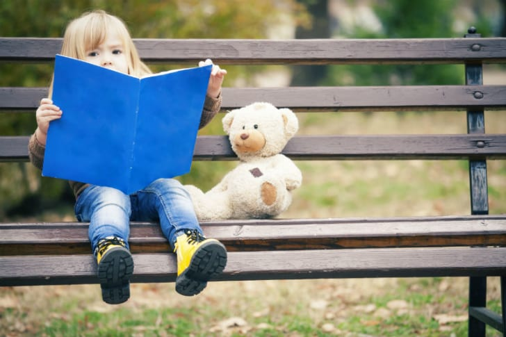 A litle girl reads while sitting on a park bench