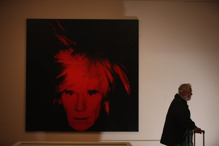 A visitor walks near Self-Portrait 1986 by artist Andy Warhol (1928-1987) at the Graves Gallery on April 11, 2012 in Sheffield, England