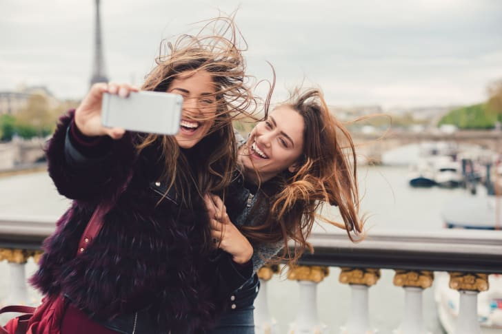 girls talking selfie in paris as wind whips their hair around