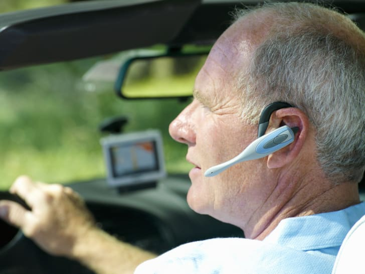 man uses bluetooth headset in car