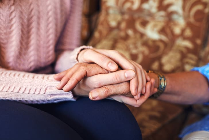 A person in a pink sweater, sitting on a couch, holding the hands of an older person
