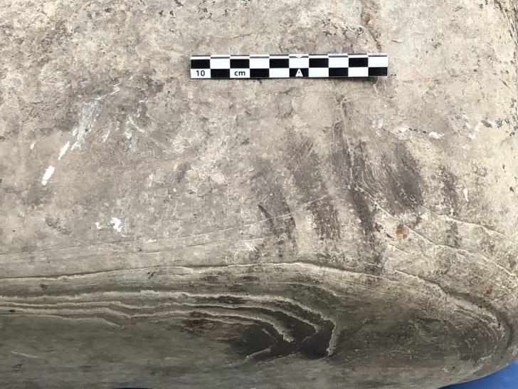 A close up of a dark handprint on a stone slab