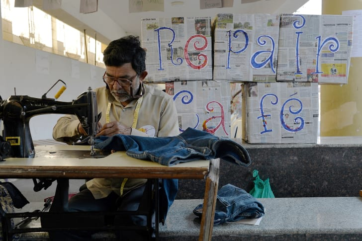 A tailor mends a pair of pants in front of a homemade sign that reads 'Repair Cafe.'