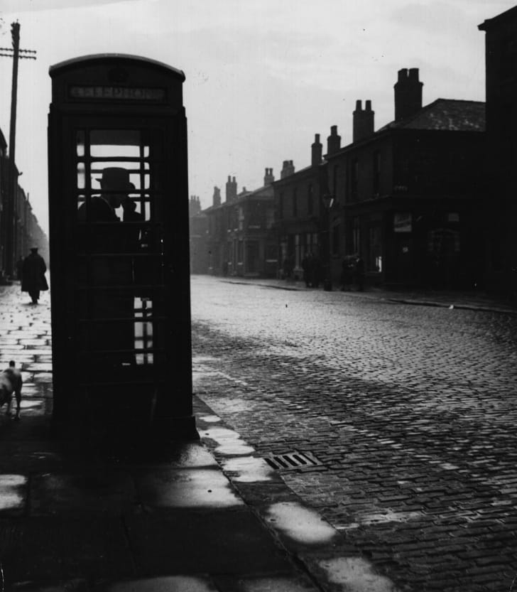 A black-and-white photo of a person making a telephone call on a UK street