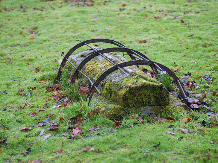 A mortsafe on a mossy grave at St Mary's Churchard, Holystone, England