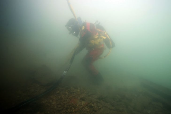 A diver works with a cable on an underwater construction job