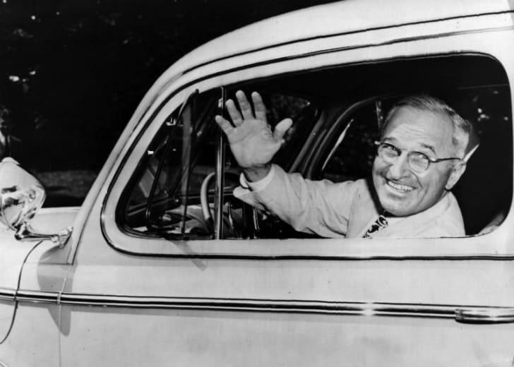 Harry Truman waves from the driver's seat of his car