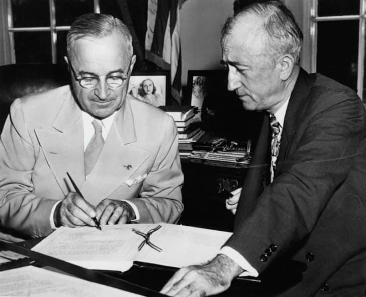 Harry Truman signs a document