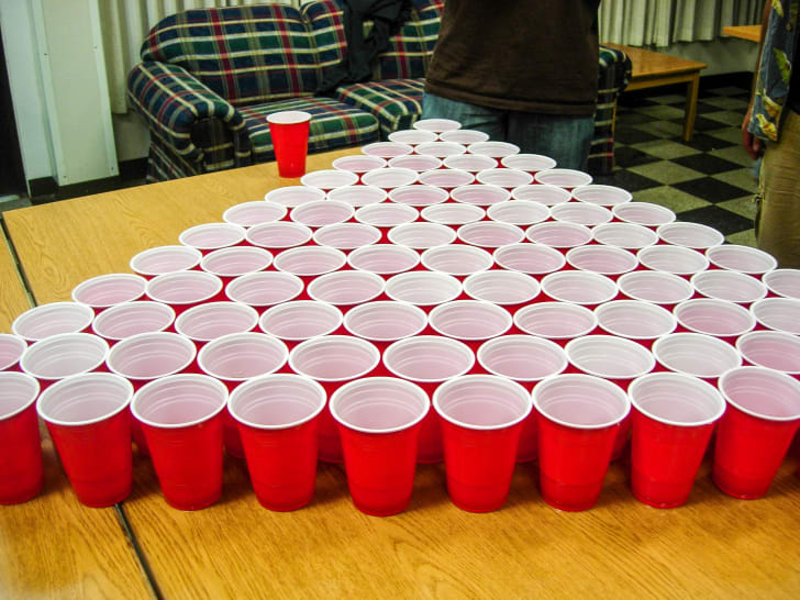 A lot of red cups set up for a game of beer pong.