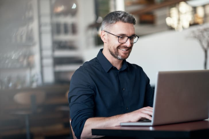 A man smiling while he types on his laptop.