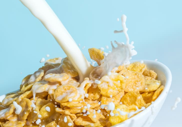 Milk being poured into a bowl of cereal.