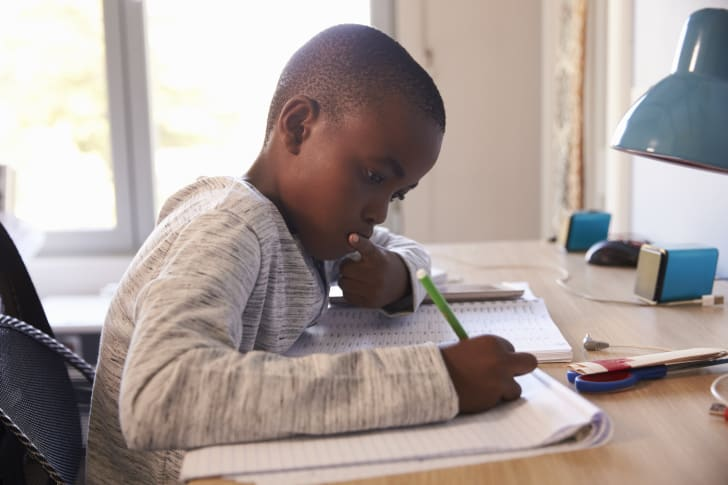 Young Boy In Bedroom Sitting At Desk Doing Homework