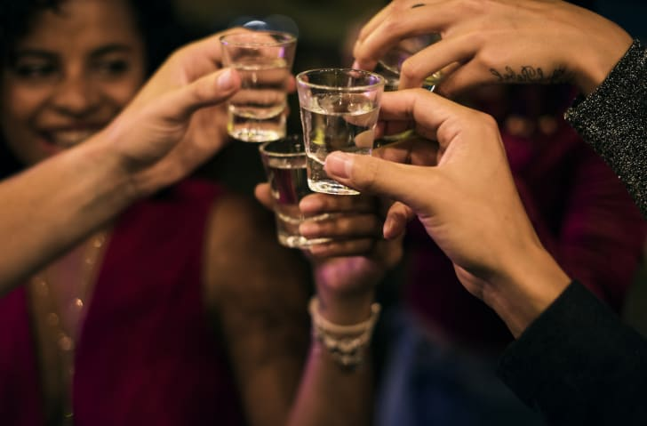 A group of people clinking full shot glasses together.