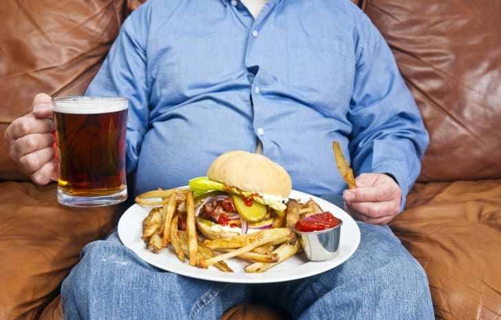 A man, shown from the neck down, sitting on a couch holding a beer with a burger and fries on a plate in his lap.