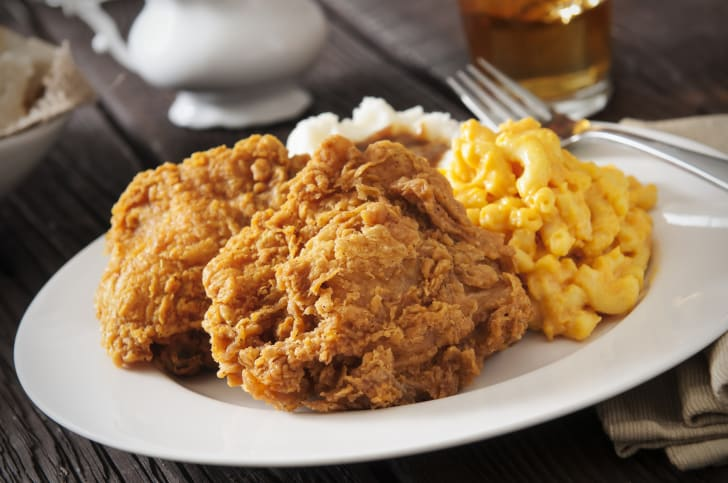 A plate of fried chicken, macaroni and cheese, and mashed potatoes.