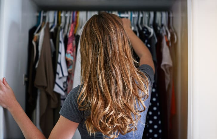 A woman, pictured from the back, looking into her closet.