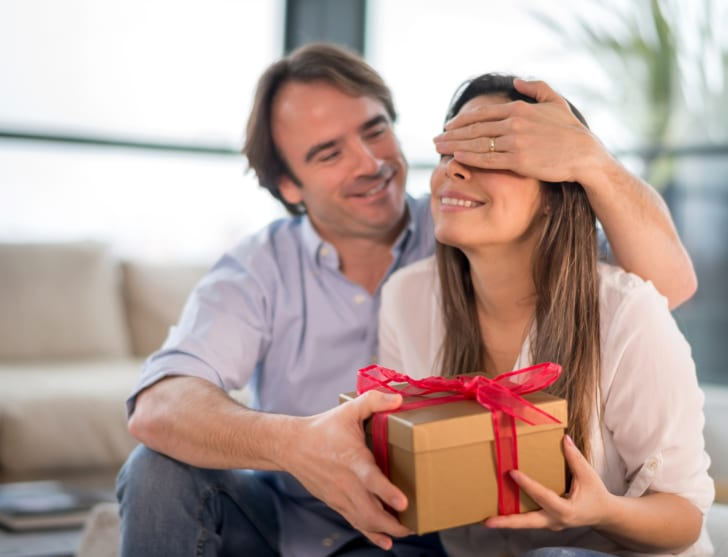 A man puts his hand over his partner's eyes as he hands her a gift.