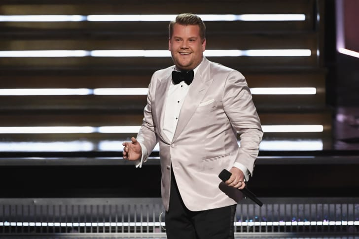 James Corden on stage in a white jacket