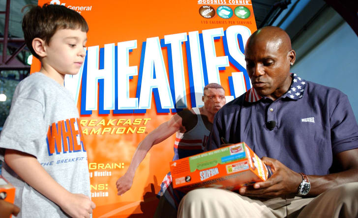 Carl Lewis signs a Wheaties box with his image on it for a young boy.
