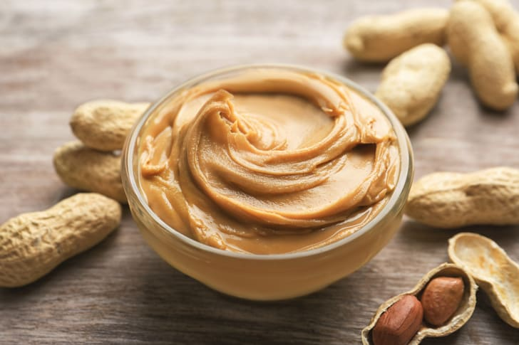 Image of peanut butter in a bowl with some whole peanuts artfully tossed around the bowl