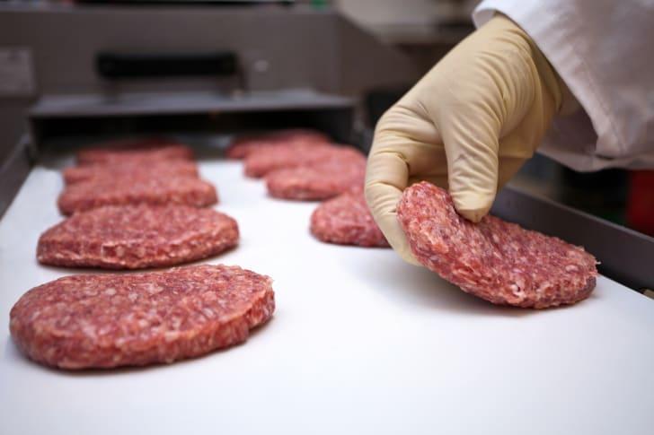 Image of a worker shaping raw hamburger patties