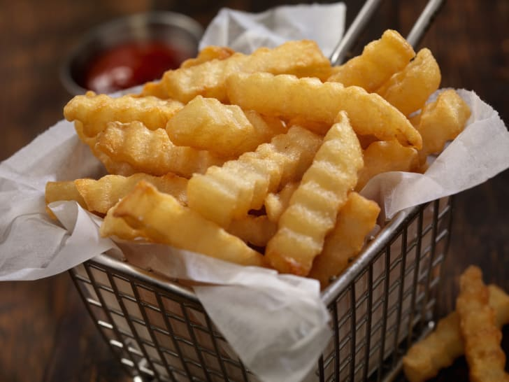 Image of crinkle cut fries fresh out of the deep fryer