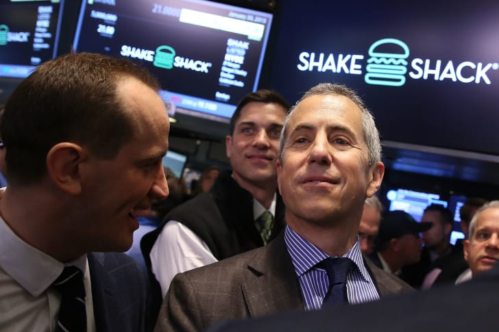 Image of restaurateur Danny Meyer smiling proudly in front of computer screens bearing the Shake Shack logo