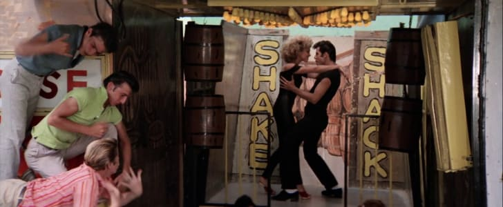Screencap of Sandy and Danny dancing on the Shake Shack ride from the 1978 movie Grease