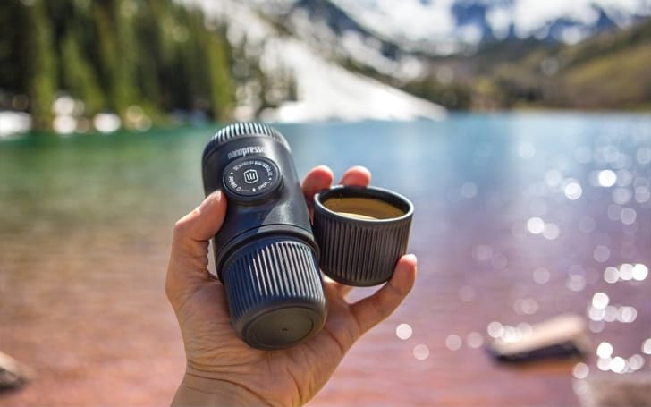 Hand holding a tiny espresso machine by a lake.