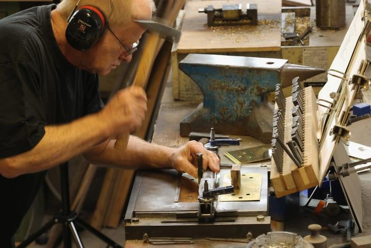A man in a shop holding a hammer making a Stolpersteine.