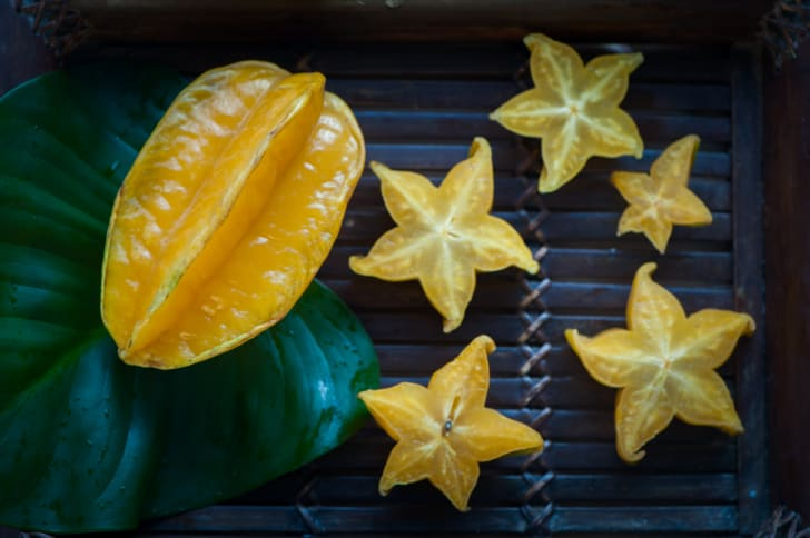 A whole star fruit with a cut up star fruit on a black background.