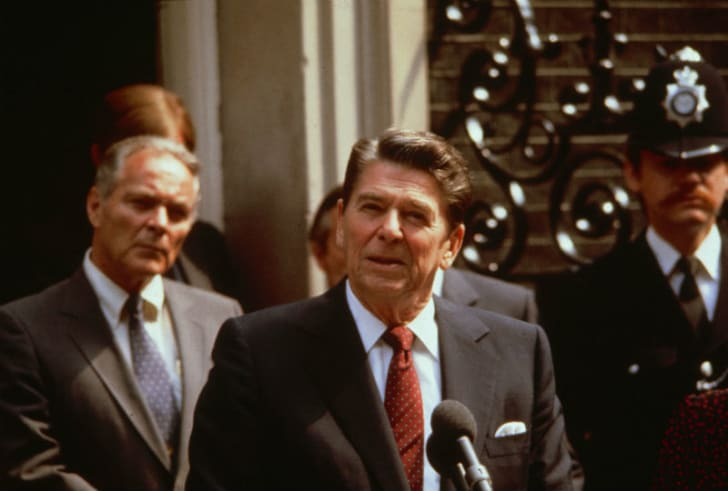 Ronald Reagan addresses a crowd from behind a podium