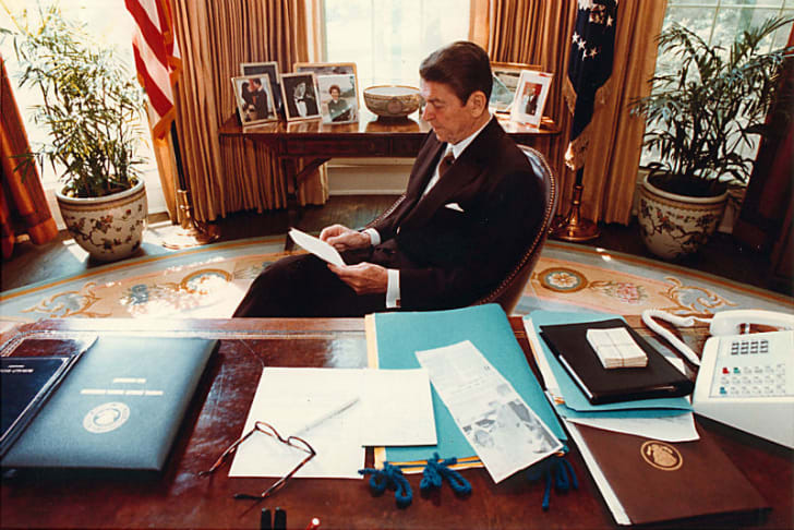President Ronald Reagan sits behind his desk in the Oval Office
