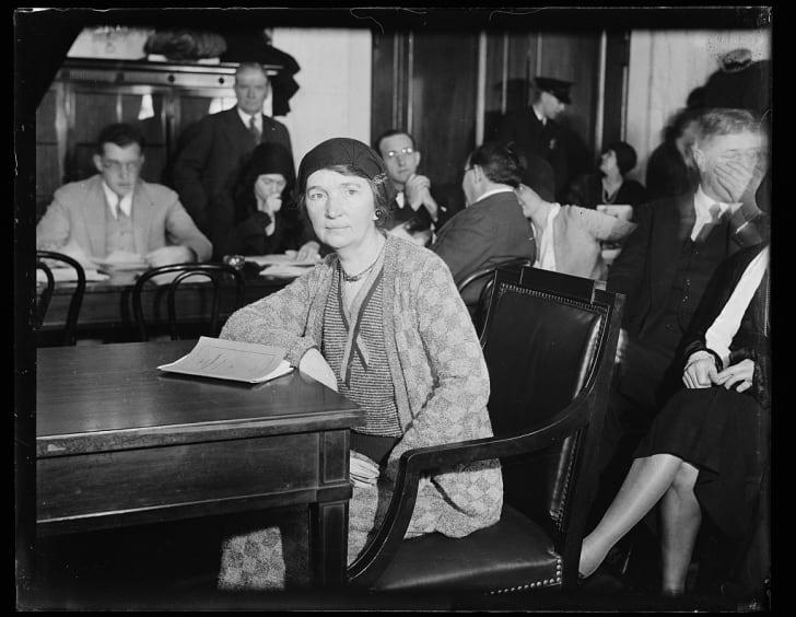 Margaret Sanger sitting at a table.