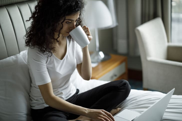 woman drinks from cup and uses laptop on hotel bed