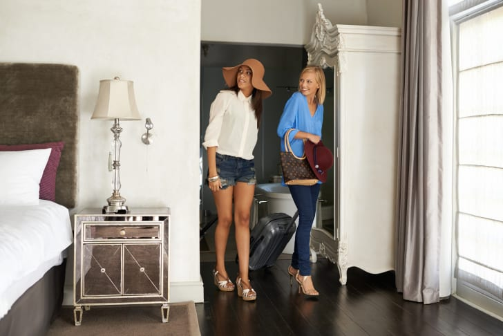 two women enter hotel room with suitcases