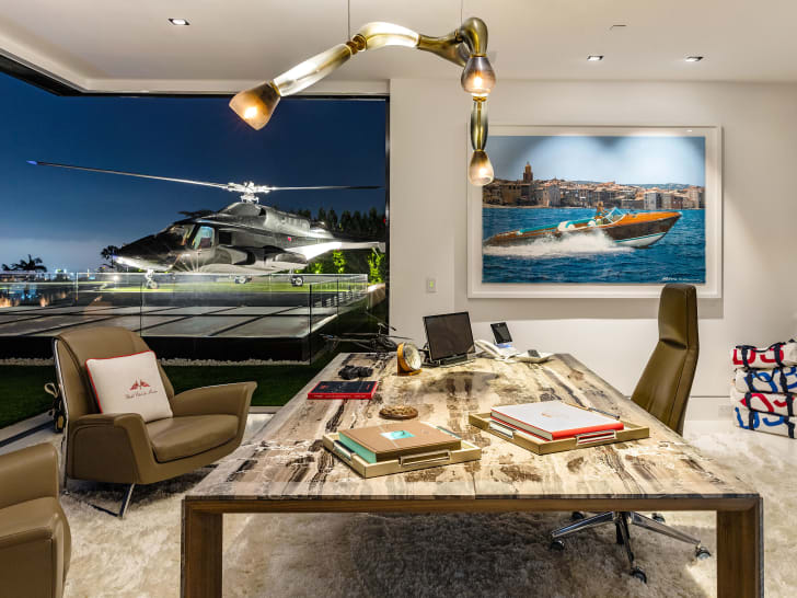 An office desk looks out on a helicopter sitting on the lawn at night.