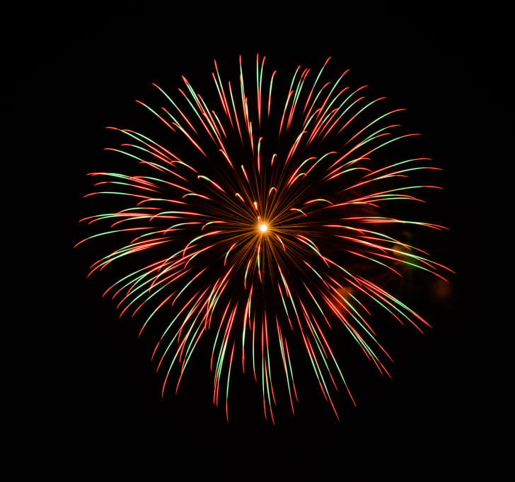 A red and green firework bursting in the night sky